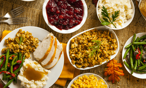 Food Dishes Turkey, Cranberrys, Stuffing, Greens on a wood table
